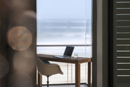 Laptop on desk in modern home office overlooking ocean - CAIF18797