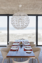 Set table in modern dining room overlooking ocean - CAIF18800