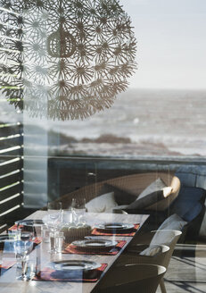 Set table in modern dining room overlooking ocean - CAIF18809