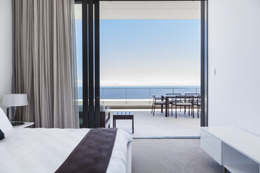 Modern bedroom and balcony overlooking ocean - CAIF18974