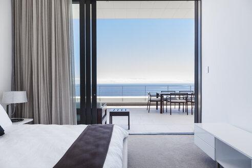 Modern bedroom and balcony overlooking ocean - CAIF18974