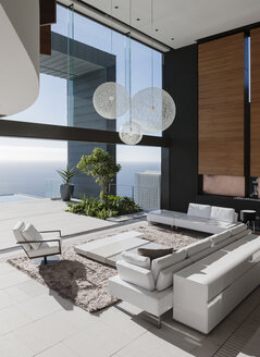 Modern living room overlooking ocean - CAIF18989