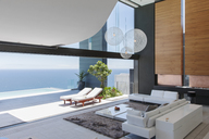 Living room and patio of modern house overlooking ocean - CAIF19001