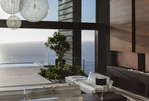 Sofas and tables in modern living room overlooking ocean - CAIF19016