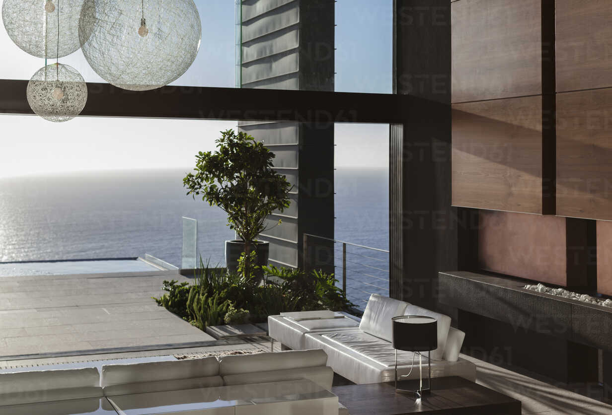 Sofas and tables in modern living room overlooking ocean - CAIF19016 - Astronaut Images/Westend61