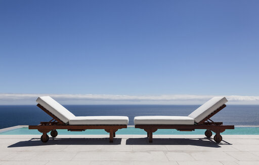 Lounge chairs and infinity pool overlooking ocean - CAIF19025