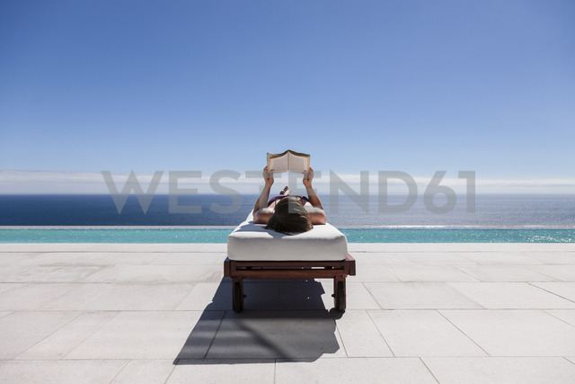 Woman reading on lounge chair at poolside overlooking ocean - CAIF19037 - Astronaut Images/Westend61