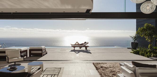 Woman sunbathing on lounge chair at poolside overlooking ocean - CAIF19040