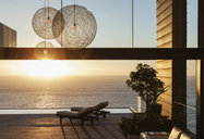 Patio of modern house overlooking ocean at sunset - CAIF19043