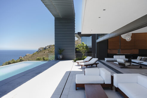 Lounge chairs and infinity pool on modern patio overlooking ocean - CAIF19049