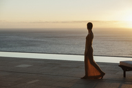 Woman looking at ocean from modern patio at sunset - CAIF19055