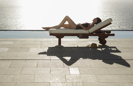 Woman sunbathing in lounge chair at poolside overlooking ocean - CAIF19058