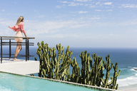 Woman standing on poolside balcony overlooking ocean - CAIF19091