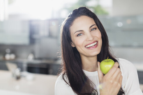 Portrait of smiling woman eating apple in kitchen - CAIF19118