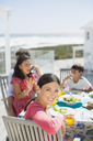 Family eating lunch at table on sunny patio overlooking ocean - CAIF19298