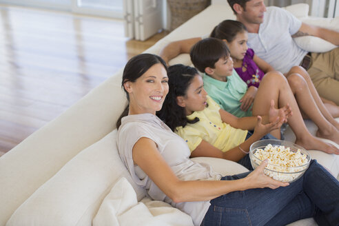 Family watching movie on sofa in living room - CAIF19331