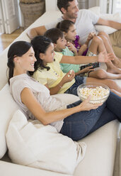 Family watching movie on sofa in living room - CAIF19334