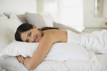Woman hugging pillow on bed - CAIF19349