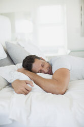Man hugging pillow on bed - CAIF19358