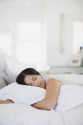 Woman hugging pillow on bed - CAIF19370