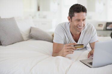 Man shopping online with laptop on bed - CAIF19373