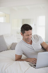 Man using laptop on bed - CAIF19379