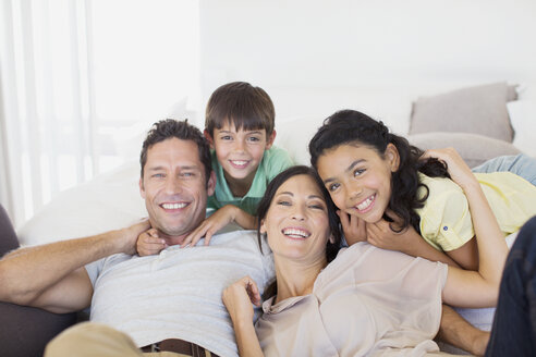 Family smiling together on sofa in living room - CAIF19382