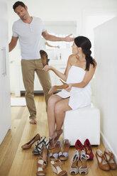 Man helping girlfriend choose shoes in bedroom - CAIF19385