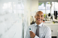 Businessman smiling at whiteboard in office - CAIF19412