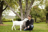 Happy man with goat on grassy field - CAVF09524