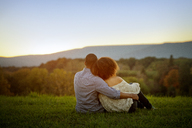 Rear view of couple sitting on grassy field during sunset - CAVF09566