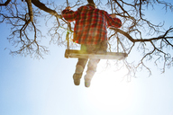 Low angle view of boy sitting on swing - CAVF09638