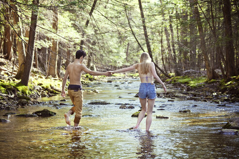 Young couple holding hands while walking in stream - CAVF09716