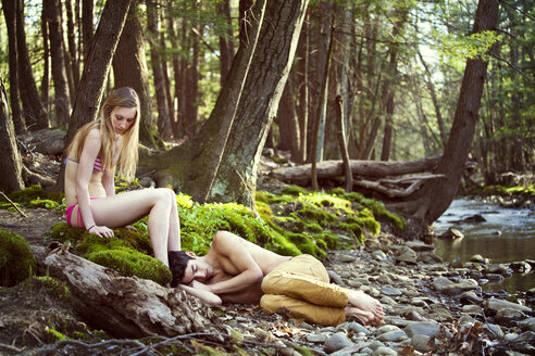 Couple relaxing at riverbank in forest - CAVF09731
