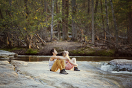 Couple looking up while sitting on rock by river at forest - CAVF09740