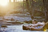 Woman lying on boyfriend at forest - CAVF09743