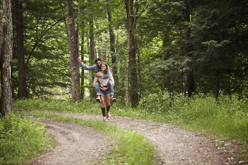 Woman piggybacking man while walking on dirt road in forest - CAVF09836