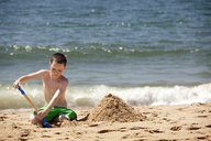 Boy playing with sand at beach - CAVF09854