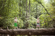Brothers fishing while standing on fallen tree trunk in forest - CAVF09866