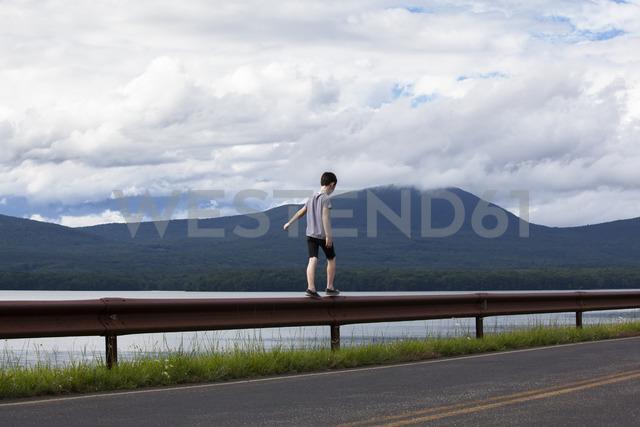 Rear view of boy walking on railing against sea - CAVF09884