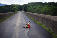 Boy falling from skateboard on road by retaining wall - CAVF09890