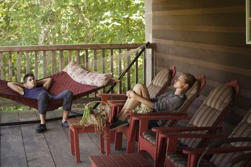 Couple relaxing on porch at home - CAVF09917