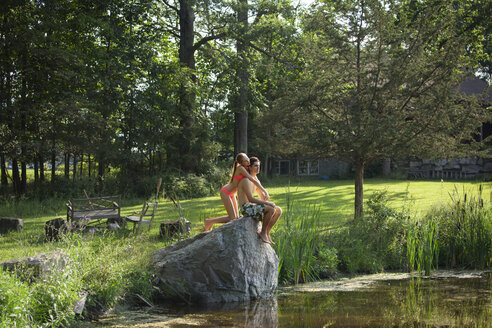 Couple sitting on rock at lakeshore - CAVF09929