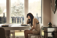 Side view of woman sitting on chair by table at home - CAVF09956