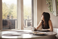 Woman looking away while sitting by breakfast table at home - CAVF09959