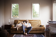 Couple relaxing on sofa at home - CAVF09965