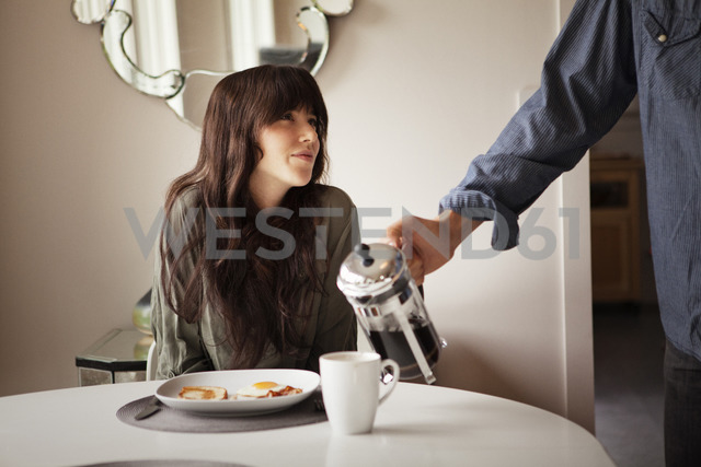 Cropped image of man pouring coffee in cup for girlfriend at home - CAVF09968