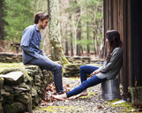 Full length of couple sitting by cottage - CAVF09977