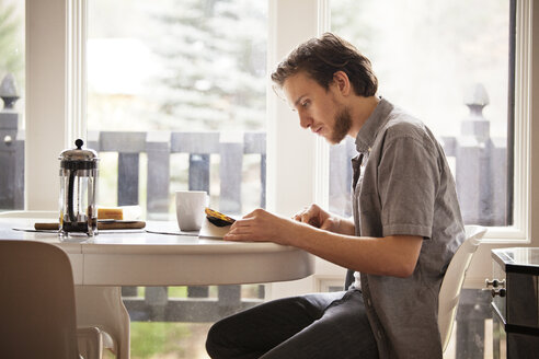 Man reading magazine while sitting on chair by breakfast table at home - CAVF09980