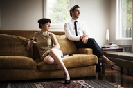 Couple looking away while sitting on sofa at home - CAVF09995